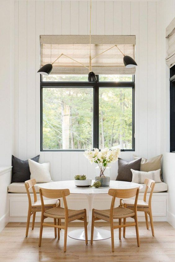 white round top dining table wood dining chairs white bench seat with throw pillows glass windows with black trims modern pendants with black lampshade light wood floors