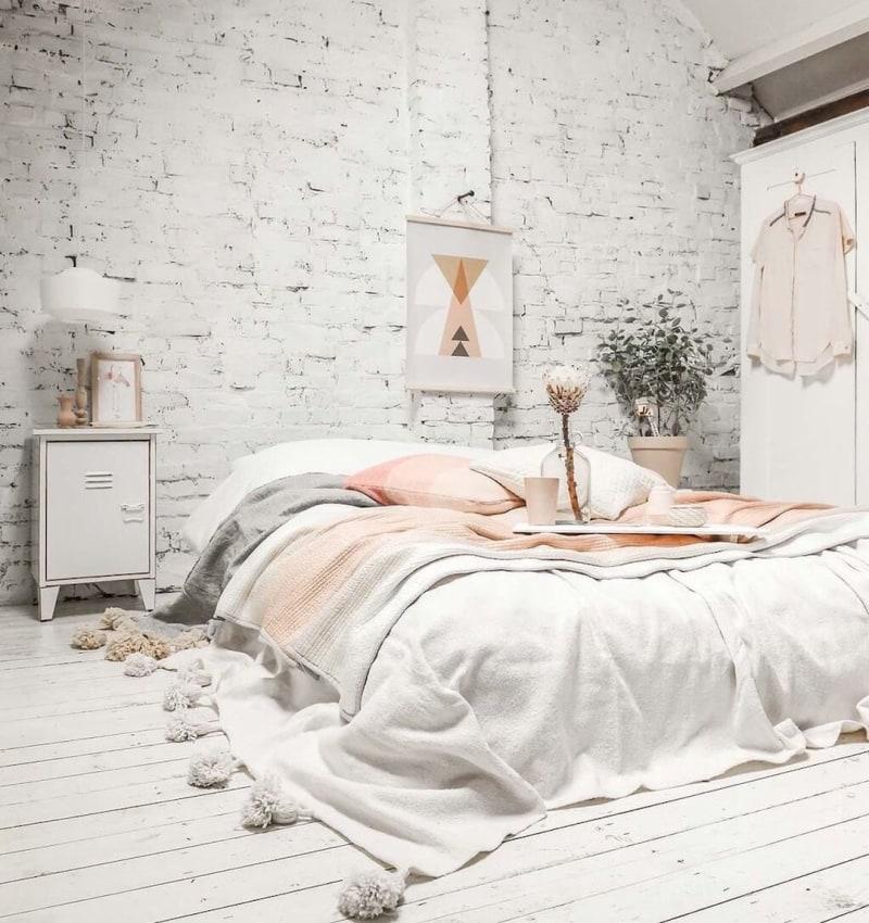 whitewashed brick walls whitewashed wood plank floors white duvet cover with pom pom ornaments