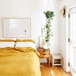 Yellow Bed Linen Wood Floors Wooden Bedside Table Hanging Greenery On Black Pot Wood Framed Painting