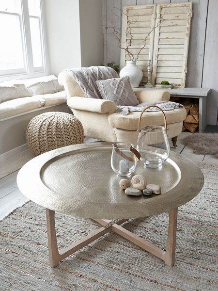 Moroccan coffee table with lightweight metal top in round shape with layers of textures and patterns light wood legs