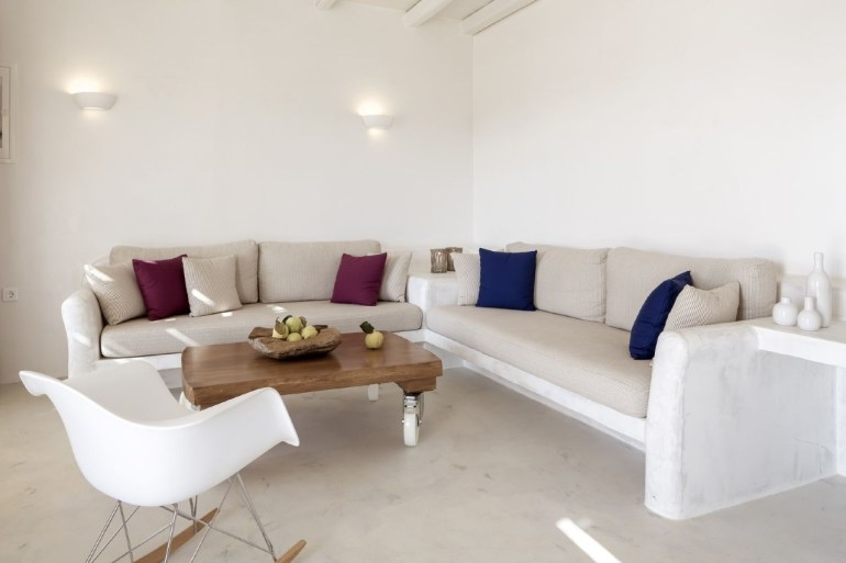 all white living room idea soft broken white sofas with deep blue and purple throw pillows movable wooden coffee table white rocking chair