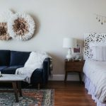 Area Rug With Layers Of Bold Colors And Patterns Midcentury Modern Coffee Table And Sofa White Fury Throw Blanket With Tassels A Couple Of Bohemian Wall Decors
