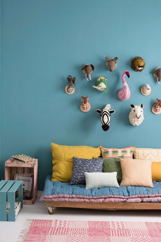 bright blue walls accented with animal stuffs movable low profile daybed with colorful throw pillows decorative crates for sit