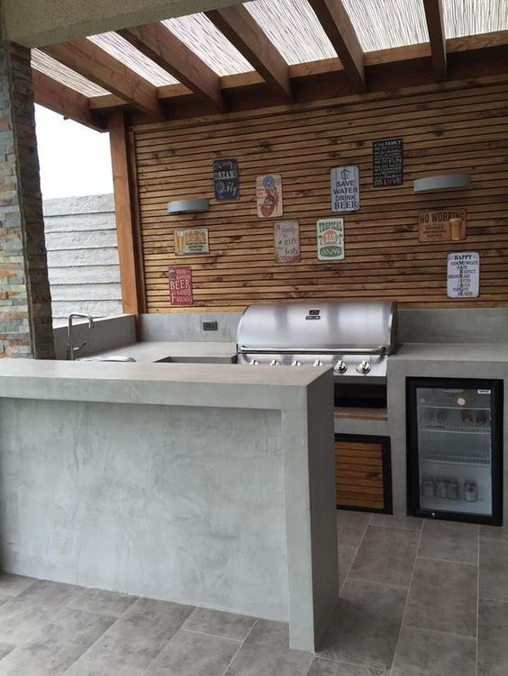 industrial minimalist outdoor kitchen idea concrete tiled floors concrete kitchen counter wood plank walls stainless steel utensils