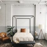 Modern Industrial Bedroom Black Wrought Iron Bed Canopy Bench Bed With Black Leather Cushion Worn Out Area Rug Leather Corner Chair Tripod Leg Floor Lamp White Painted Brick Walls