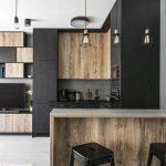 Modern Industrial Kitchen Design Black Matte Cabinetry Wooden Cabinetry Wooden Bar Tables Black Plastic Bar Stools White Tile Floors Industrial Pendants Clean White Ceilings