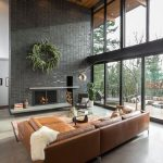 Open Plan Interior In Modern Industrial Style Black Tiled Walls With Recessed Modern Fireplace Leather Modular Sofa Glass Top Coffee Table Oversized Glass Windows Exposed Wood Ceilings
