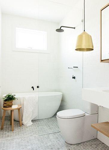 ultra modern minimalist bathroom modern white bathtub light wood stool brass finish pendant hexagon tiled floors in light tone