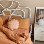 Vintage Style Bedroom With Unique Headboard And Poppy Orange Bedding Treatment
