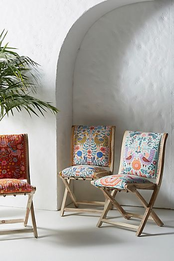 wood framed chair with x base and colorful floral print upholstery