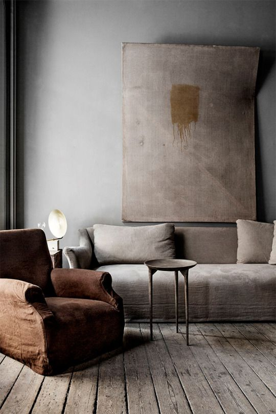 worn out yet warm living room gray sofa dark brown armchair abstract wall decor gray washed wood plank floors