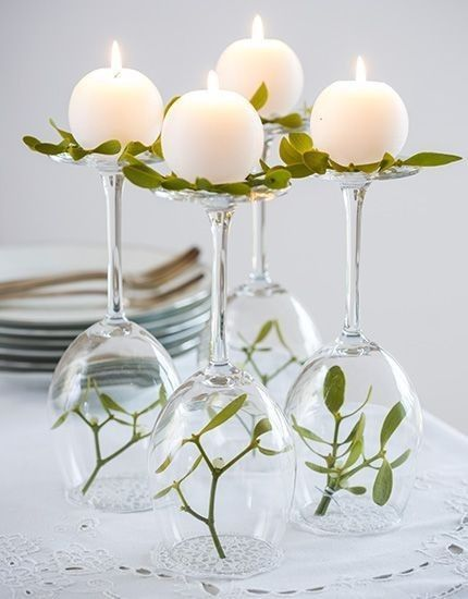DIY greenery centerpiece consisting of upside down wine glass greenery and ornate candles