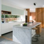 Nordic Style Kitchen Design Clean Line Kitchen Cabinets In White White Countertop Full Glass Kitchen Backsplash Marble Kitchen Island In White A Couple Of Modern Bar Stools With Round Wood Top
