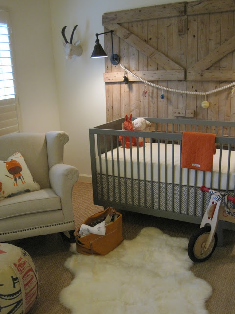 antique wood barn door panel as the backdrop gray baby crib superlight gray nursery chair sheepskin rug in white