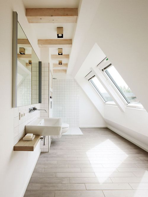attic bathroom with exposed wood beams floating white sink supported with wood panel as the countertop frameless mirror whitewashed wood plank floors glass windows as the skylights