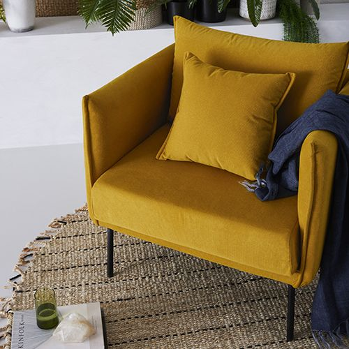 bold yellow accent chair with yellow throw pillow flat woven area rug in round shape with fringes