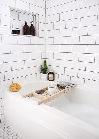 caddy for drink and book soak bathtub in white white subway tile walls white hexagon tile floors recessed shelf for bath supply
