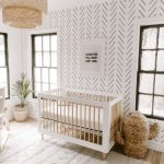 Crisp White Baby Crib With Wood Color Accent Oversized Boho Pendant White Textured Area Rug Modern Patterned Wallpapers Wood Floors