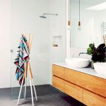 Floating Wooden Vanity With White Countertop And Double White Sinks Extra Large Frameless Mirror Walk In Shower With Clear Glass Doors And Walls Wooden Towel Stand Herringbone Tile Floors In Black