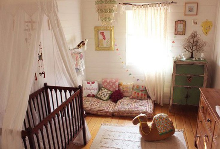 floor cushions with throw pillows white area rug animal stuff dark wood baby crib with canopy and white drape oak plank floors