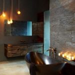Glossy Black Bathtub Stainless Faucet Black Stone Walls Dark Wood Vanity Cabinets Frameless Mirror Warm Toned Lighting Fixtures