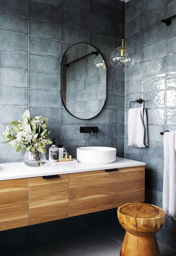 glossy watery blue tile walls wooden bathroom vanity with white countertop and sink wooden stool black framed mirror faucet and towel hangers