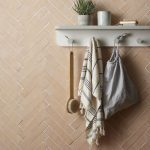 Herringbone Tile Walls In Pastel With White Grouts White Hanger And Shelf
