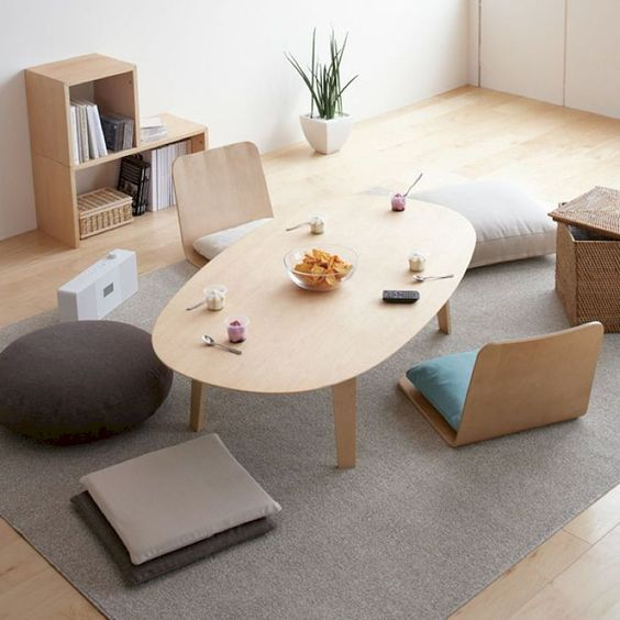 informal living room idea floor seat with throw pillows light wood coffee table gray area rug light wood shelving unit