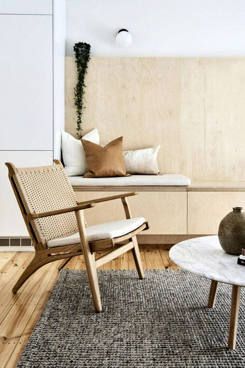 light wood chair with thin white cushion textured gray area rug round marble top coffee table with wood legs light wood bench with throw pillows