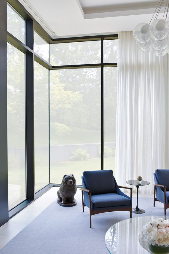 lighter window curtains in white glass windows with black wood trims stunning ceiling lamps modern blue chairs glass top coffee table in round shape