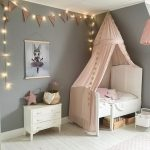 Little Girl's Room White Bed Frame With Headboard White Dresser Gray Walls With String Lamp Ornament White Wood Plank Floors Blush Pink Bed Drapery