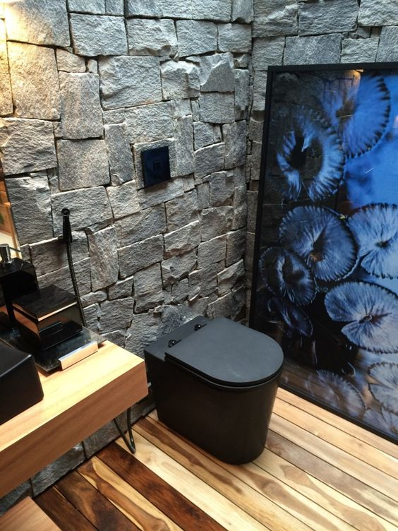 masculine bathroom stoned walls wood plank floors wood bathroom vanity black toilet