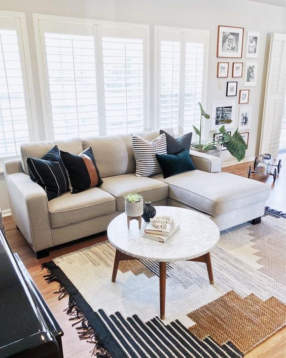 minimalist living room idea white modular sofa with throw pillows round marble top coffee table with wood legs flat woven area rug with multiple modern patterns and colors