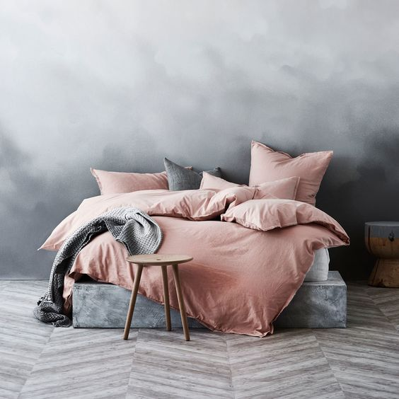 rose dust duvet cover gray washed walls concrete bed frame woven throw blanket in gray herringbone patterned wood floors wooden stool