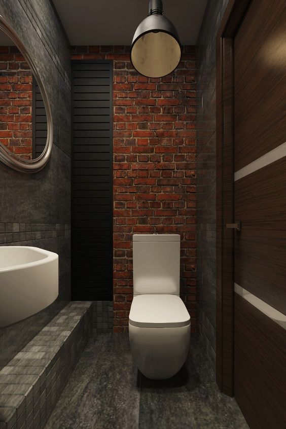 tiny bathroom red brick walls featuring matte black ornate wall black washed floors round mirror white sink white closet