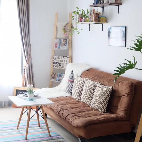 tufted upholstery sofa in earthy brown white square top coffee table in modern minimalist style corner wood ladder rack