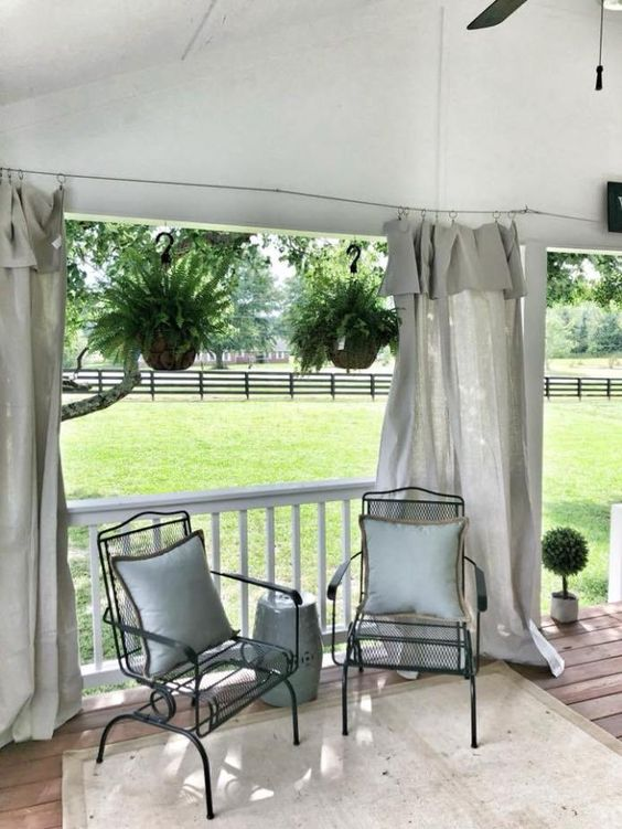 veranda with wood plank floors white rug black wrought iron chairs white throw pillows drop cloth as the curtains in white