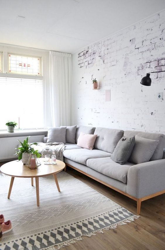 whitewashed brick wall Scandinavian style furniture set light toned area rug with fringes wooden floors