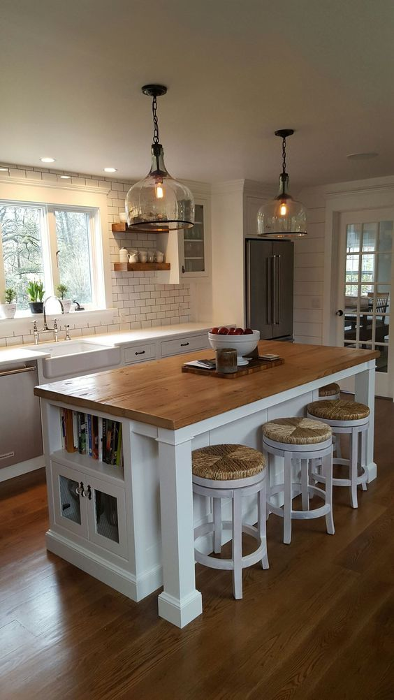 wood top kitchen island with book shelf and storage solution some bar stools white subway tiled walls and backsplash with dark grouts white countertop farmhouse sink