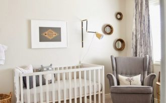 woodprint wallpaper on ceiling crisp white walls white baby crib light brown shag rug brown pouf gray nursery chair