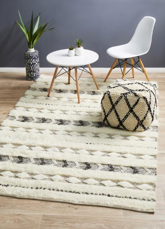 Evaana area rug with geometric patterns Scandinavian chair and table geometric patterned pouf