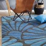 Isha Modern Rug With Blue Patterns And Gray Color Backdrop Leather Chair With X Base Blue Floor Pillow