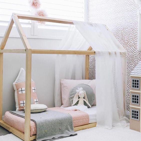 Montessory floor bed made from natural pine crisp white draperies white bed linen pink toddler blanket gray blanket
