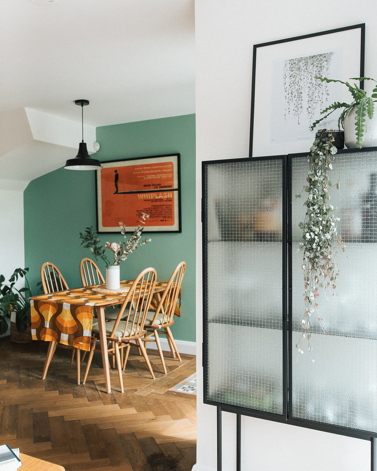 aqua color walls bold orange wall decor with black frame rattan dining chairs in midcentury modern style colorful table runner herringbone wood plank floors