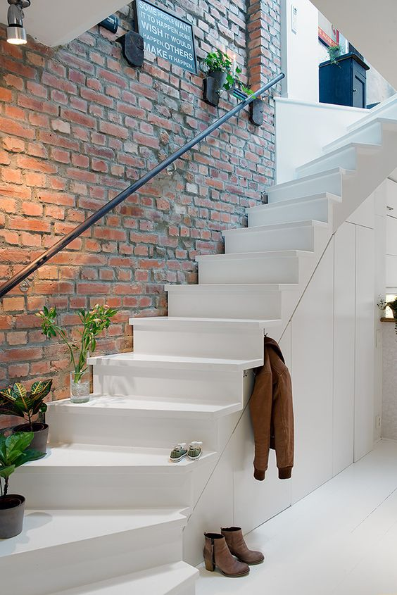 barely red brick wall white contemporary stairs with black iron handy