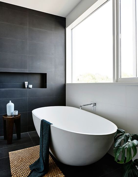 black tile wall with recessed shelf modern style dark wood stool modern white bathtub handwoven wood mat white wall with glass window houseplant