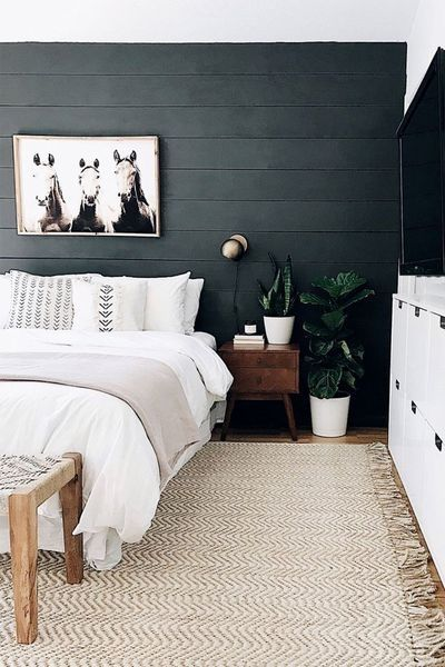 black wood walls dark wood nightstand in midcentury modern style white area rug with tassels white bedding treatment white media stand