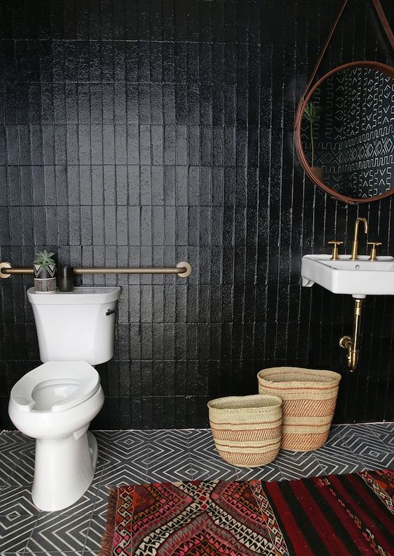 bold black tile walls white toilet brass finish piping ornate handwoven baskets wall mounted sink in white with brass faucet tribal runner with colorful motifs