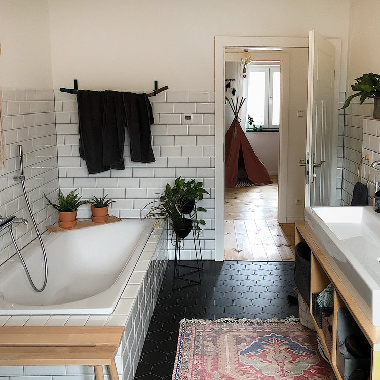 built in bathtub in white subway ceramic tile walls in white hexagon tile floors in black worn out runner