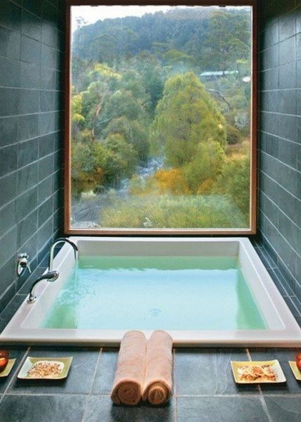 built in soaking tub in square shape dark tile walls and floors fully glass window with wood frame